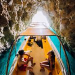 Boat and young adults in Comino Cave