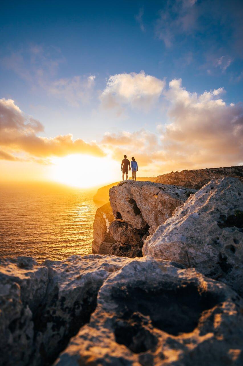 Couple on cliffs of Malta at Sunset