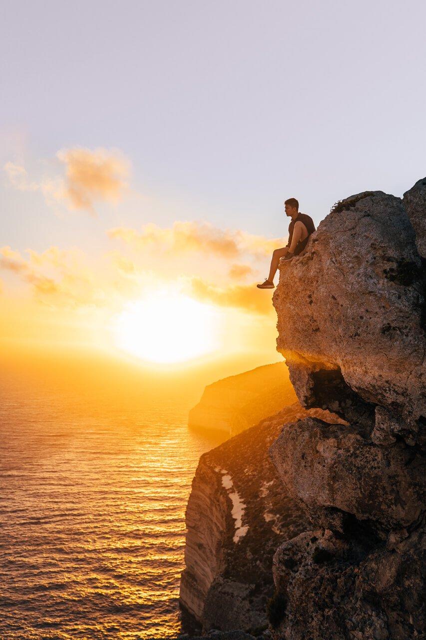 Guy on cliffs of Malta at Sunset