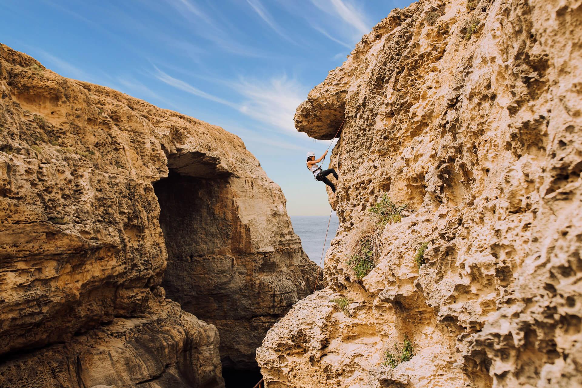 Young Woman climbing cliffs of Gozo